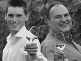 Auf dem Bild sieht man den Weinbautechniker Andreas und den Winzermeister Heinfried Peth die dem Betrachter mit einem Glas Weisswein aus dem Weinberg Zuprosten.